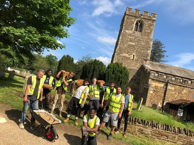 Stonemason Martin, left, with wheelbarrow and Dean, second from right, with the trainees